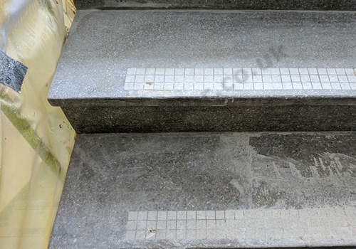 Dusty terrazzo stairs mid-refurbishment in an apartment block