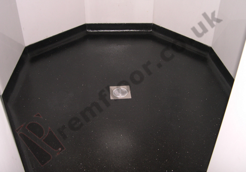 Black resin terrazzo shower tray with drain in middle
