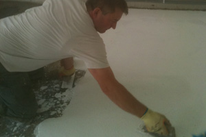Operative hand laying an epoxy resin terrazzo screed using trowel onto a sand & cement screed