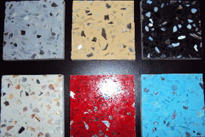 Samples of resin terrazzo including black, red, blue, and beige backing with mirror glass and mother of pearl aggregates