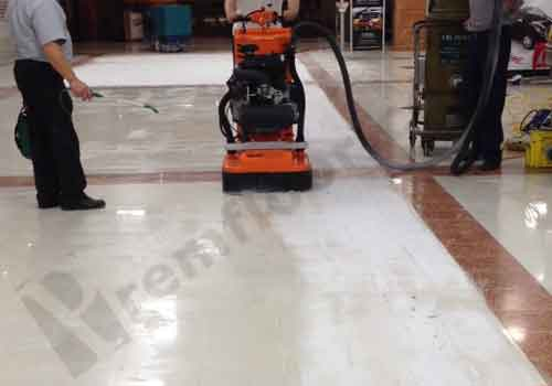 Operatives in a shopping centre grinding terrazzo tiles to clean & restore anti-slip