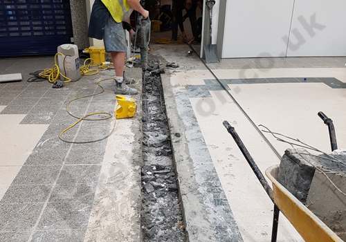 Operative breaking out screed from channel in floor
