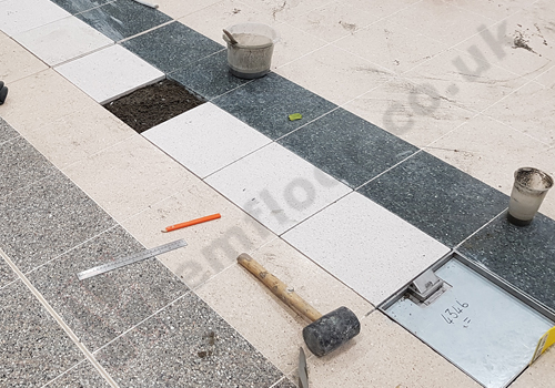 Terrazzo tiles over sand & cement screed into a trench leading to floor box