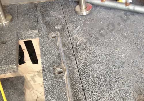 Holes in black terrazzo floor after removing a hand rail
