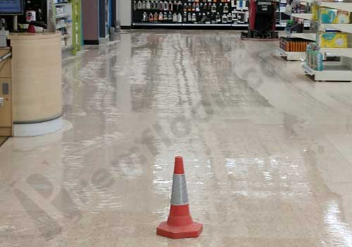 Water on terrazzo floor during polishing works in supermarket