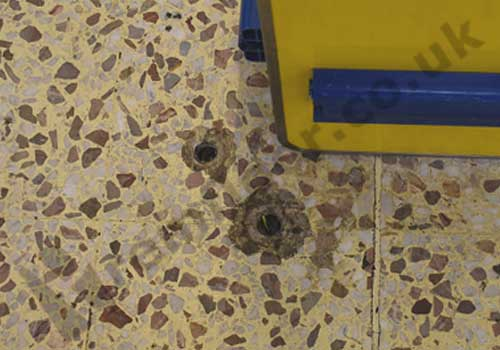 Holes in supermarket terrazzo floor tile from bumper rail being removed