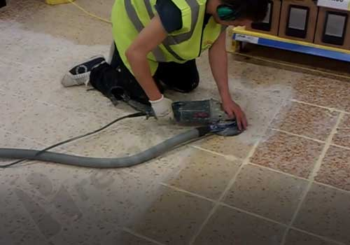 Grinding terrazzo grout from joints in a grid shape on supermarket floor
