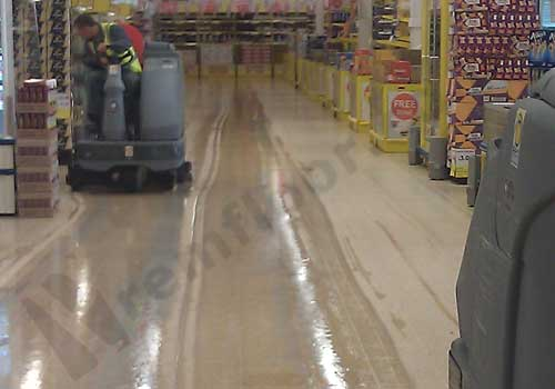 Nilfisk scrubber dryers fitted with diamond floor pads polishing a supermarket aisle