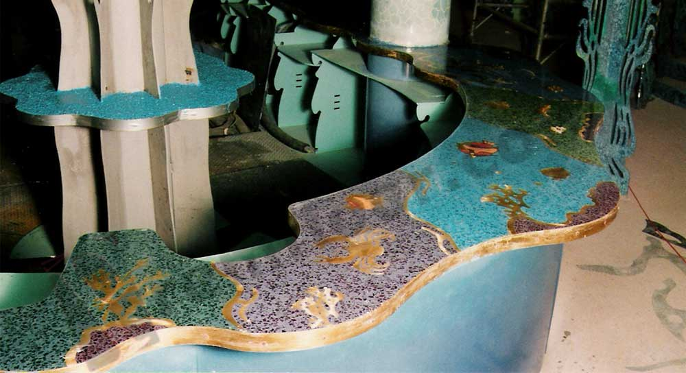 Bar in nightclub with blue resin terrazzo countertop featuring sea creatures and underwater creatures