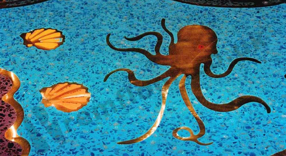 Sea creatures and shells cut from brass in a blue resin terrazzo bar top