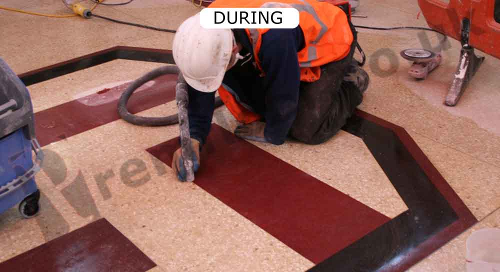 Cleaning the red part of the terrazzo floor pattern of upminster bridge station