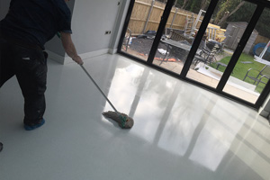 A white resin terrazzo floor being sealed in kitchen